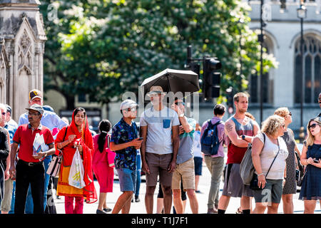 London, UK - June 25, 2018: People many crowd crowded standing by Westminster Abbey church building square tour group Indian tourists waiting to cross - Stock Photo