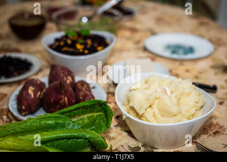 Table with setting of healthy vegan vegetarian Thanksgiving dinner and green vegetables romaine lettuce salad and mashed potatoes with sweet Japanese  - Stock Photo