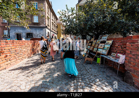 Warsaw, Poland - August 22, 2018: Famous old town historic street in city during sunny summer day and red orange brick wall fortress people walking on - Stock Photo