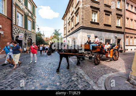 Warsaw, Poland - August 22, 2018: Historic buildings and horse carriage tour in old town during day and guide man wide angle view - Stock Photo