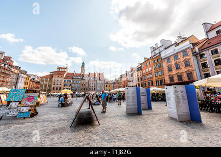 Warsaw, Poland - August 22, 2018: Historic cityscape with view of colorful architecture buildings in old town market square with museum signs - Stock Photo