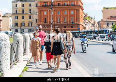 Rome, Italy - September 4, 2018: People tourists walking on sidewalk on summer sunny day near Colosseum while sightseeing by street with cars, scooter - Stock Photo