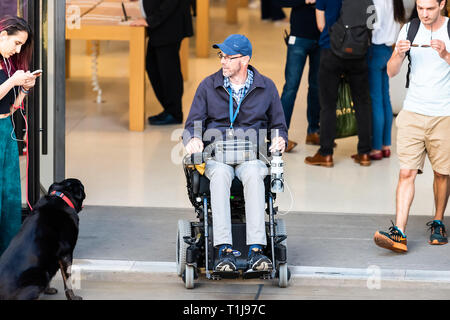 London, UK - June 22, 2018: Disabled man sitting in wheelchair or electric scooter by store, shop building entrance with people walking - Stock Photo