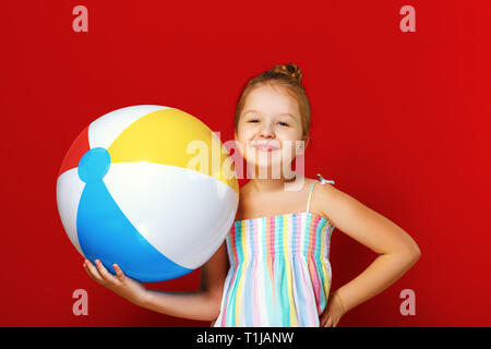 Portrait of a cheerful happy little child girl in summer dress with a inflatable ball. Red colored background. The concept of summer. - Stock Photo