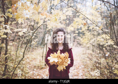 Beautiful girl with curly dark hair in a maroon top in an autumn park holding maple leaves and smiling - Stock Photo