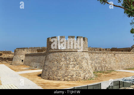 Ruins of medieval citadel Othello Castle. View on walls and a tower with coat of arms with a flying lion. Famagusta, Northern Cyprus - Stock Photo