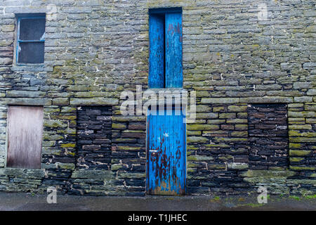 Exterior shots of the old brick work buildings in and around the royal burgh of Wick harbour, closed blue doors access caithness scotland - Stock Photo