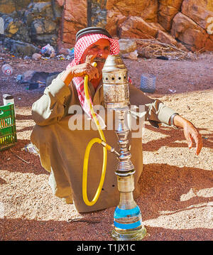 DAHAB, EGYPT - DECEMBER 16, 2017: The portrait of the senior Bedouin, smoking hookah, sitting on the sand in shade of the red rocks of the Small Color - Stock Photo