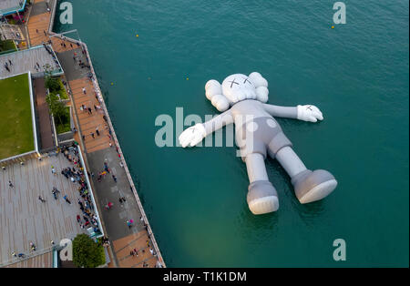 Hong Kong, China. 26th March, 2019. American artist and designer Brian Donnelly, Kaws Holiday Installation is currently on display floating in Hong Kong at the waterfront on Victoria Harbour. Hong Kong, China. Credit: Bob Henry/Alamy Live News - Stock Photo