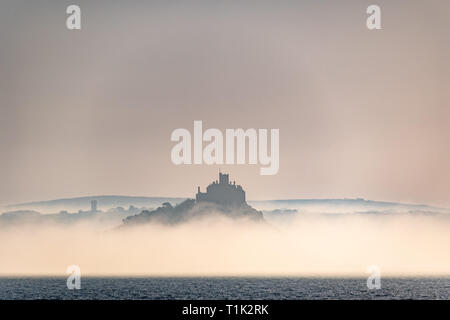 Penzance, Cornwall, UK. 27th Mar, 2019. UK Weather. Shortly after sunrise sea mist formed on the surface of the sea at Mounts Bay, shrouding the base of St Michaels mount. Credit: Simon Maycock/Alamy Live News - Stock Photo