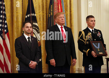Washington, District of Columbia, USA. 27th Mar, 2019. United States President Donald J. Trump presents a posthumous Medal of Honor to the family of Staff Sergeant Travis Atkins during an East Room ceremony at the White House, in Washington, DC, Wednesday, March 27, 2019. Atkins' son, Trevor Oliver, received the award, along with his grandparents. Staff Sergeant Atkins earned the award for his selfless act in Iraq, 2007, where he shielded fellow soldiers from a suicide bomber, saving the lives of three Credit: Martin H. Simon/CNP/ZUMA Wire/Alamy Live News - Stock Photo