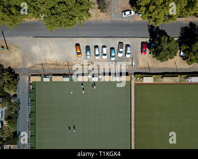 Outdoor bowling green and Australian cityscape aerial view showing an urban landscape with homes, people, asphalt street and parked cars. - Stock Photo