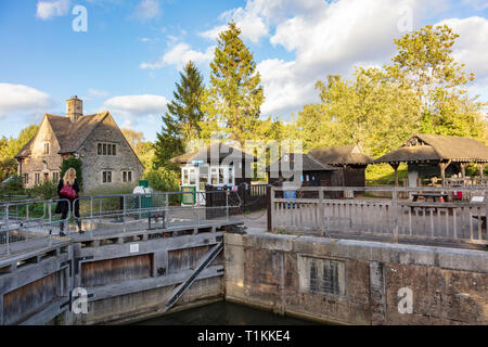 A blonde woman crosses the lock gates at Iffley Lock, Oxford, Oxfordshire, UK on the River Thames - Stock Photo