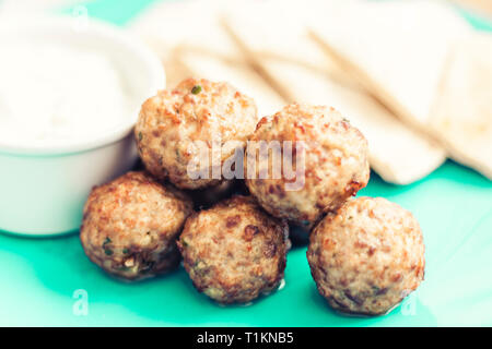 Fried minced meat with sauce and tortillas, traditional Greek lunch on a green plate in a restaurant - Stock Photo