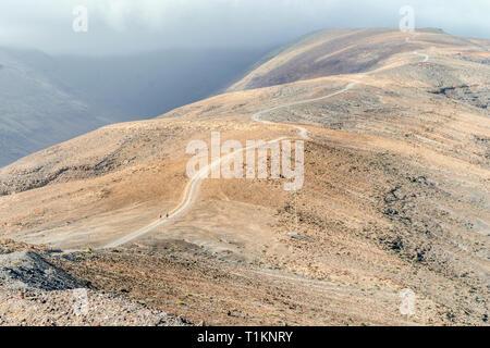 Two hikers on trail to Pico de la Zarza - the highest peak of Fuerteventura island, Spain - Stock Photo