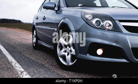 Close up front of new silver car parking on the road - Stock Photo
