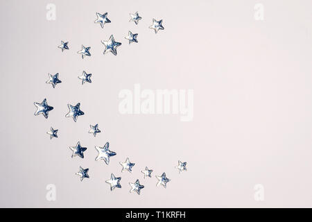 Beautiful Crescent concept made of shining silver stars with embossed transparent top on white background. Copy space. Top view. - Stock Photo