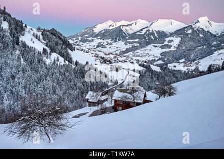 Austria, Biosphere Park Grosses Walsertal,  Raggal village and the valley covered with snow from Marul hamlet, at sunrise; bg. the peaks from the right:  Kreuzspitz (1947 m), Melkspitze (1935 m), Talispitz (2000 m), Kuhspitz (1963 m) - Stock Photo