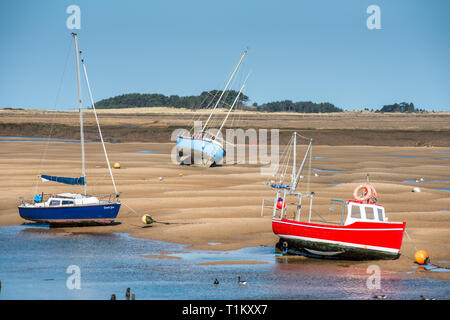Colourful boats marooned on sandbanks at low tide on East Fleet river estuary at Wells next the sea, North Norfolk coast, East Anglia, England, UK. - Stock Photo