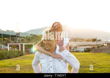 Romantic view of smiling couple in white clothes, he carries her on his back. Beautiful landscape of sun above mountain during sunset and green grass  - Stock Photo
