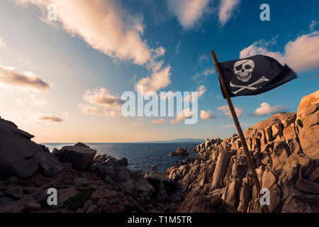 jolly roger flag flies at sunset pinned between the rocks of the pirate island in front of a few clouds in the crystal clear blue and orange sky, Capo - Stock Photo