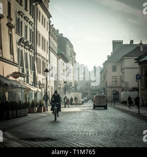 Local woman riding a bicycle down plac maryacki early in the morning with dramatic sun's rays, Krakow Poland - Stock Photo