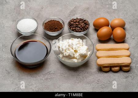 Ingredients for cooking tiramisu - Savoiardi biscuit cookies, mascarpone, cheese, sugar, cocoa, coffee and egg - Stock Photo