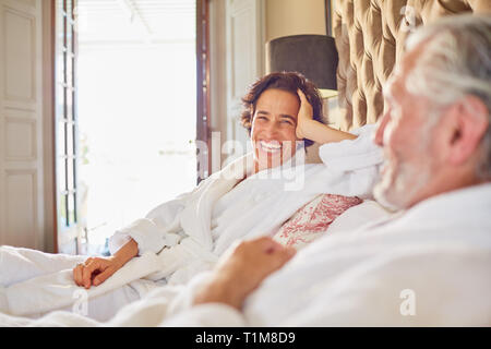 Happy, laughing mature couple relaxing on hotel bed - Stock Photo