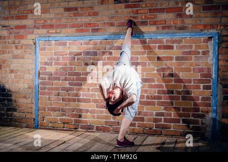 Female modern dancer performing against brick wall - Stock Photo