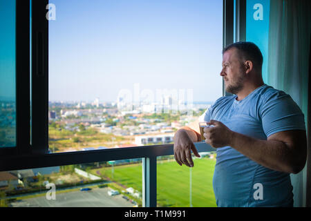 male drinks coffee and looks through  panoramic window smiles in the morning