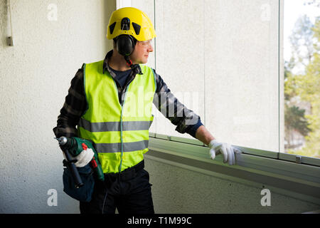 Male construction worker in hard hat with a drill and smiling at the camera. Building and renovation. - Stock Photo