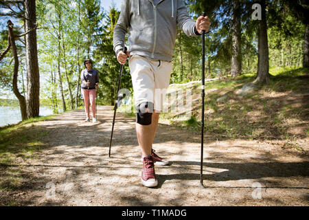 Man with bandage on knee. Rehabilitative sport in Finland - nordic walking. Man and mature woman hiking in green sunny forest. Active people outdoors. - Stock Photo