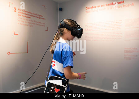 Copenhagen. Denmark. Child using a VR (virtual reality) headset to interact with an exhibit at the Danish Architecture Centre DAC, Bryghuspladsen 10. - Stock Photo