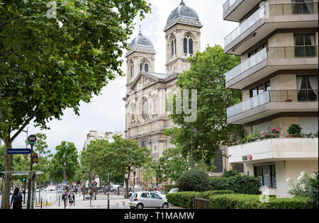 Paris, France - July 22, 2017:  Green streets of Paris in summer day. Cars on roads, people walking, beautiful architecture, cafe and shops.