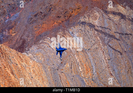 A General Dynamics F-16 Fighting Falcon flies with wings vertical through Rainbow/Star Wars Canyon in Death Valley National Park, California, USA. - Stock Photo