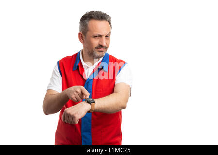 Serious hypermarket or supermarket employee pointing at wristwatch with index finger as careful time concept isolated on white - Stock Photo
