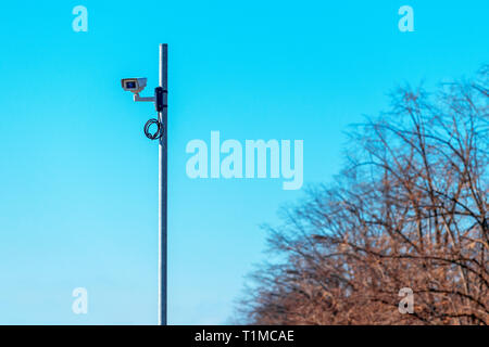 Traffic surveillance camera mounted on the post with large portion of blue sky as copy space - Stock Photo