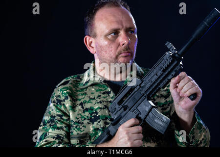 Soldier in army fatigues holding assault rifle - Stock Photo