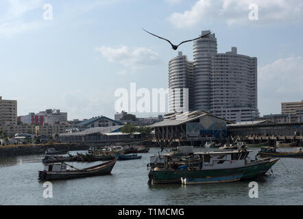 old fishing boats near fish market in Panama City with skyline background - Stock Photo