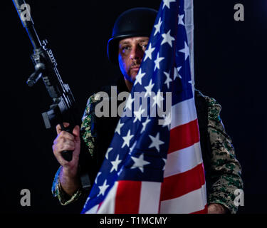Soldier in army fatigues holding assault rifle and US flag - Stock Photo