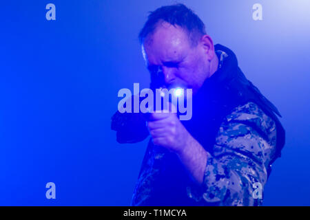 Soldier in army fatigues holding assault rifle in haze of blue smoke - Stock Photo