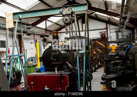 Small steam locomotive used on the Bure Valley Railway in the workshop undergoing essential repairs and maintenance - Stock Photo