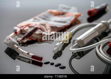 Empty blood Bag next to dropper, conceptual image - Stock Photo