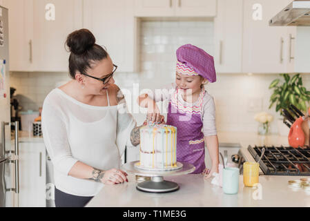 Mother and daughter decorating cake in kitchen - Stock Photo