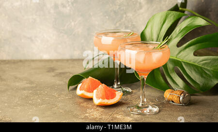 Refreshing summer cocktail grapefruit champagne rosemary juice in two glass goblets on a concrete background - Stock Photo