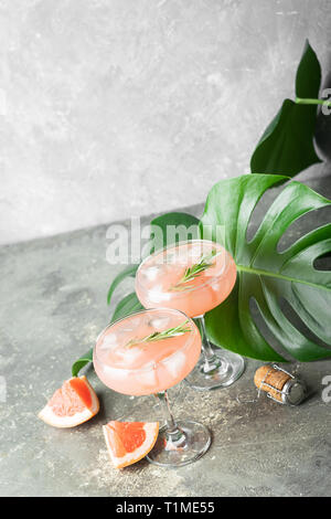 Refreshing summer cocktail grapefruit champagne rosemary juice in two glass goblets on a concrete background. - Stock Photo