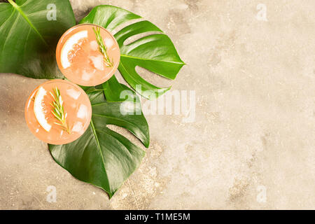 Refreshing summer cocktail grapefruit champagne juice in two glass goblets on the leaves of the Monstera plant - Stock Photo