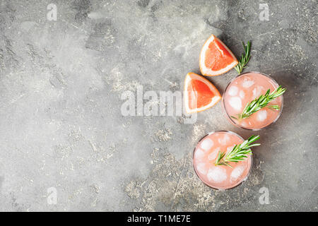 Refreshing summer cocktail grapefruit champagne rosemary juice in two glass goblets on a light gray concrete background. - Stock Photo