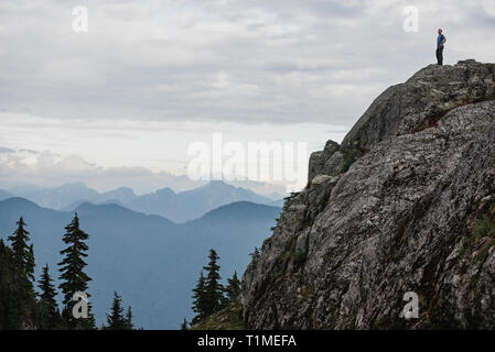 Male hiker standing on rugged mountaintop, looking at view, Dog Mountain, BC, Canada - Stock Photo