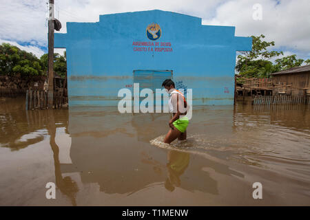 2015 flooding in Brazilian Amazon, young man passes in front of pentecostal church building Assembleia de Deus (Assembly of God) with the words 'Cristo é a Resposta' which means 'Christ is the answer', at Taquari district, Rio Branco city, Acre State. Floods have been affecting thousands of people in the state of Acre, northern Brazil, since 23 February 2015, when some of the state's rivers, in particular the Acre river, overflowed. Further heavy rainfall has forced river levels higher still, and on 03 March 2015 Brazil's federal government declared a state of emergency in Acre State, where cu - Stock Photo